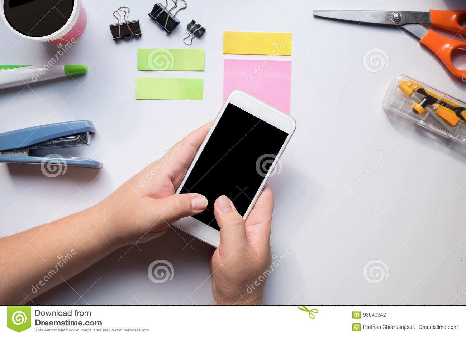 Hand using smartphone on office desk.