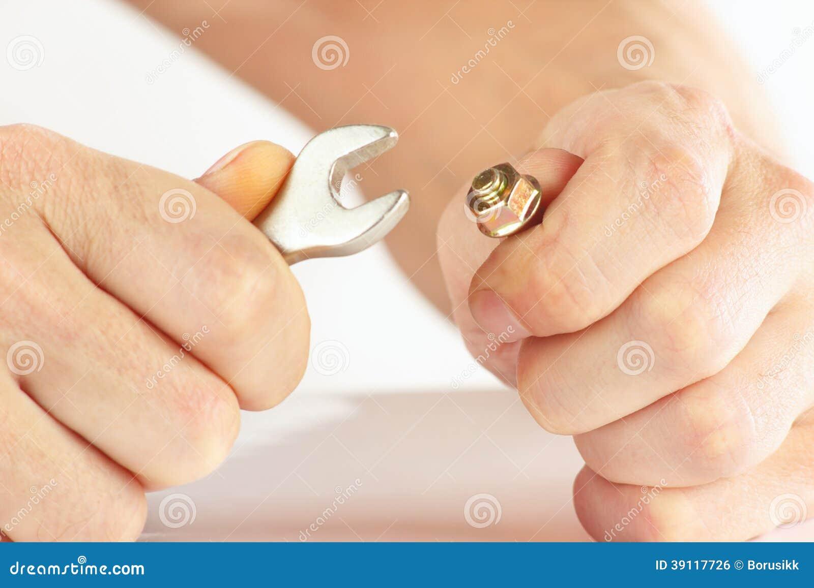 Hand van arbeider met een moersleutel om de noot aan te halen