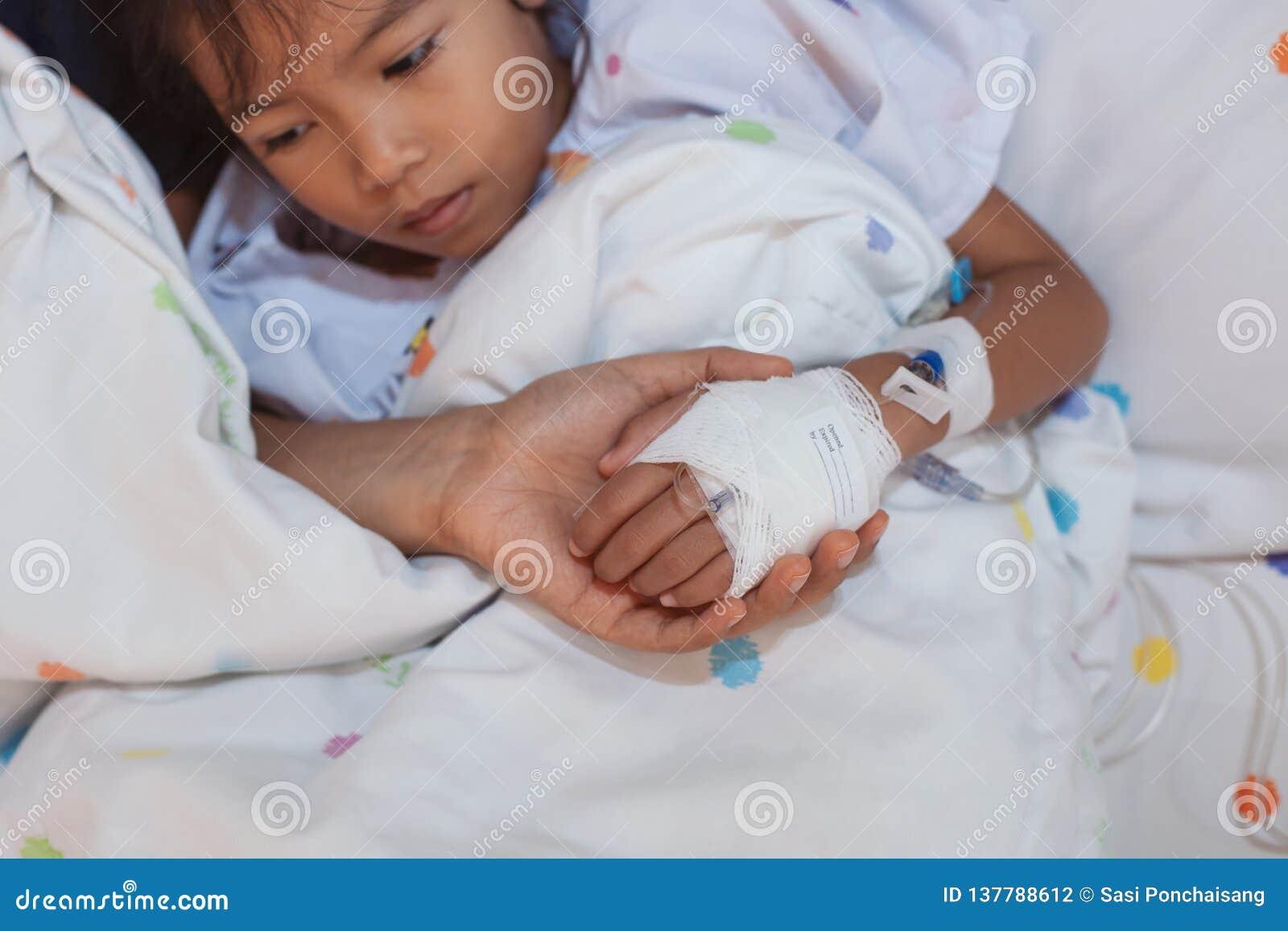 Hand van de de holdings de zieke dochter van de moederhand die IV die oplossing hebben met liefde en zorg wordt verbonden terwijl