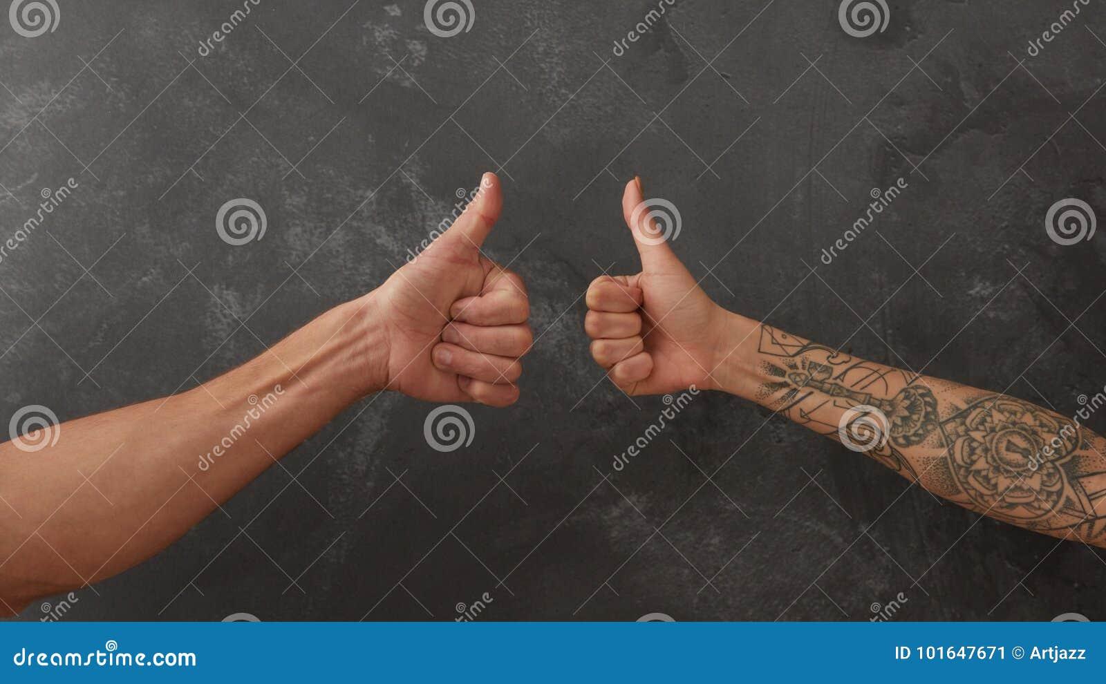 Hand van de mens en vrouwelijke hand met tatoegering