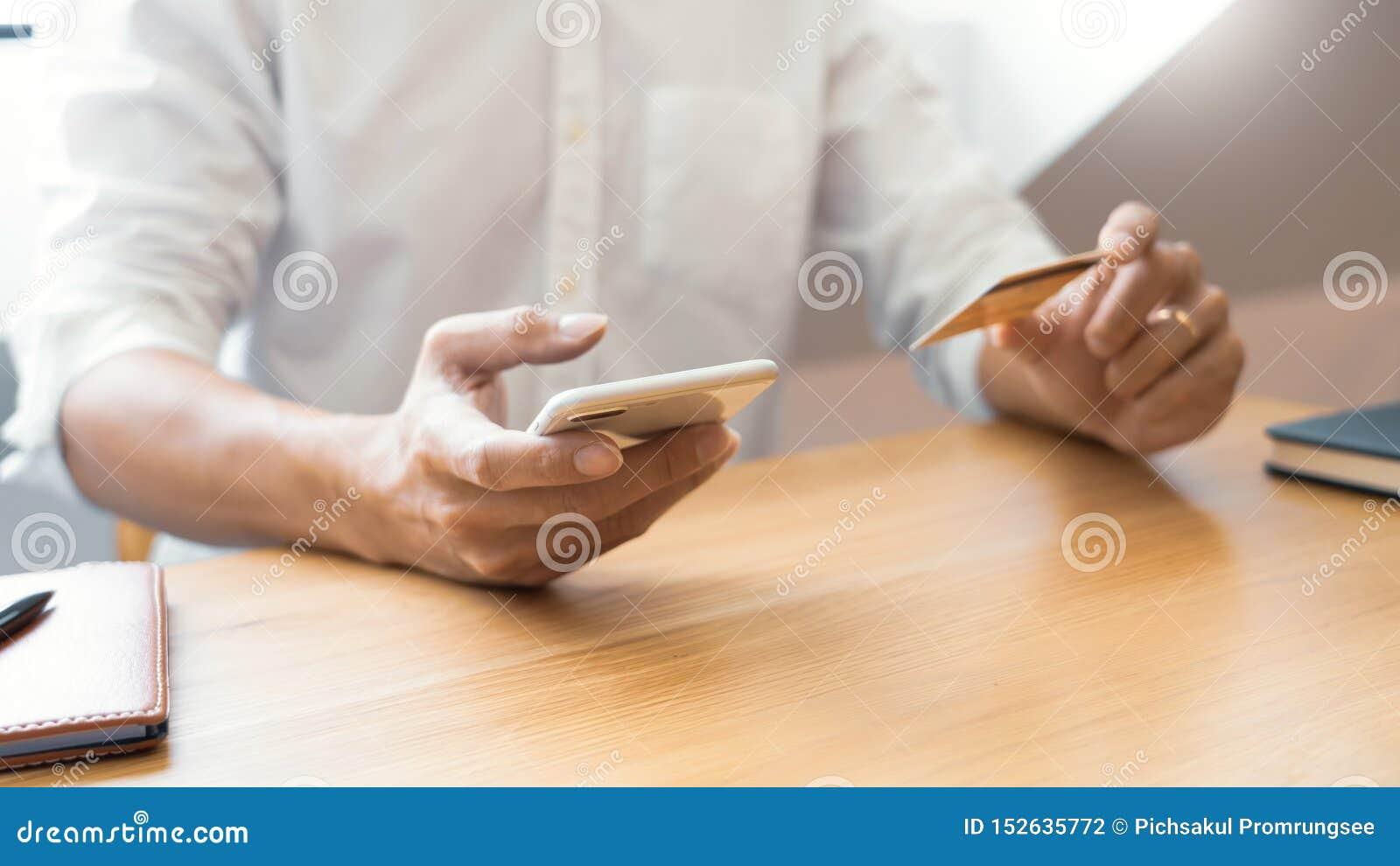 Hand van de mens in toevallig overhemd die met creditcard betalen en smartphone met behulp van voor online het winkelen makend or