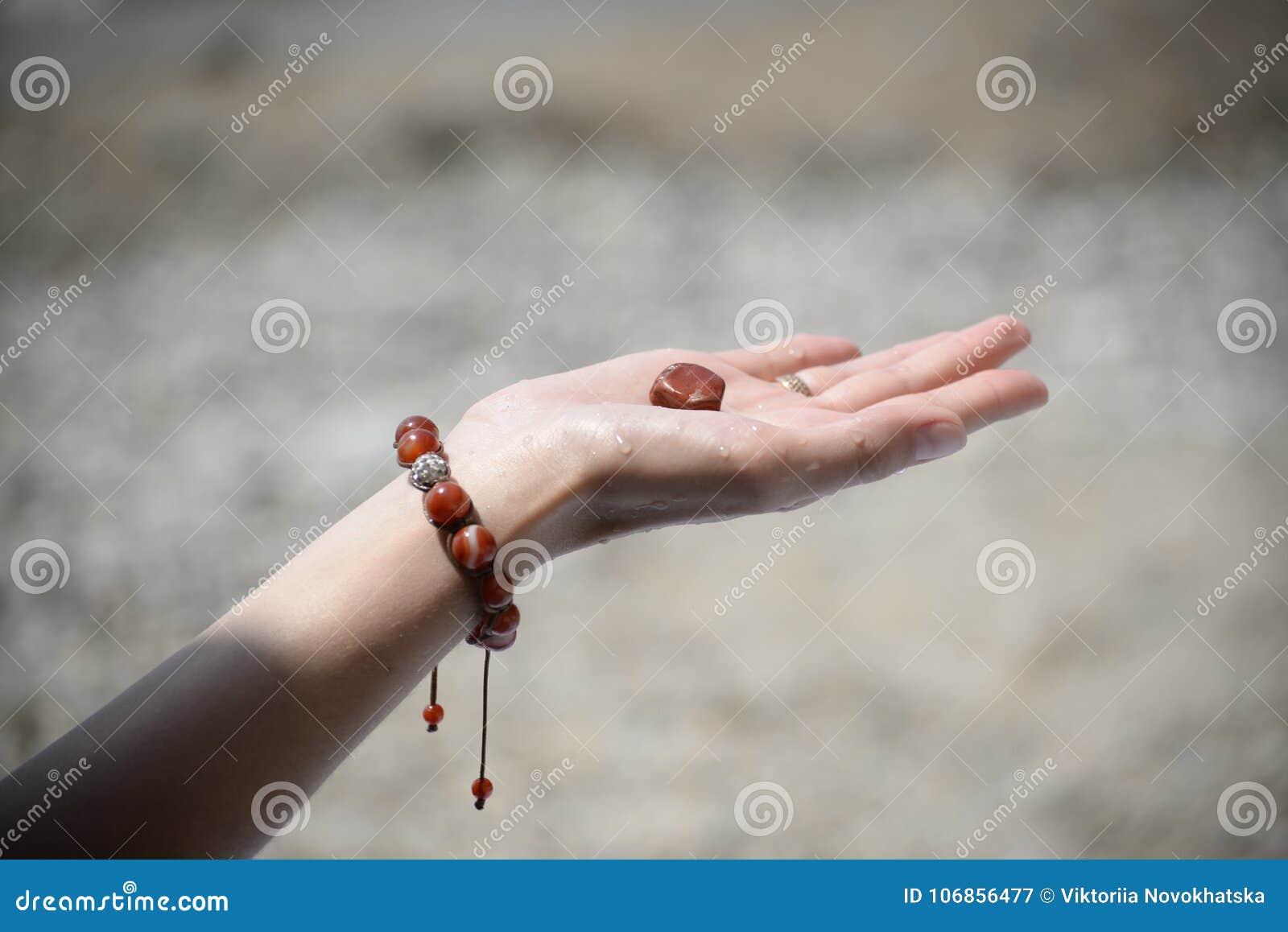 Hand van een meisje die een overzeese steen houden