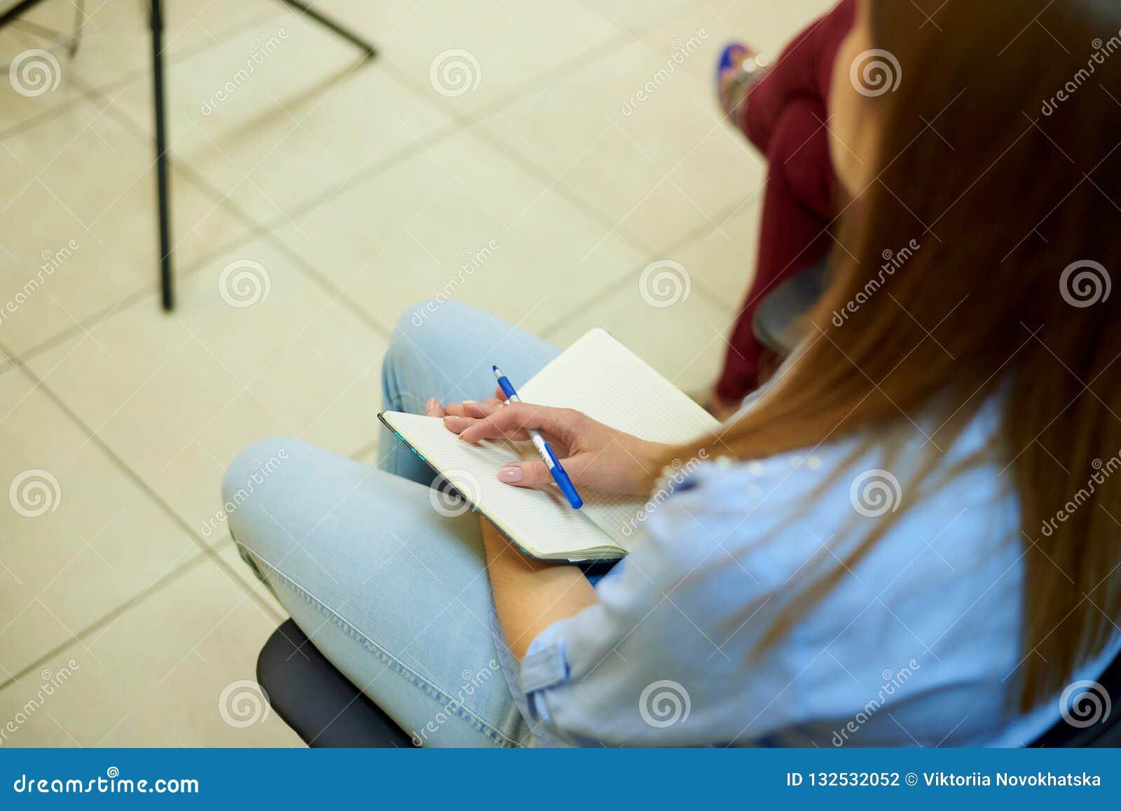 Hand van een meisje met een pen op een lege witte blocnote