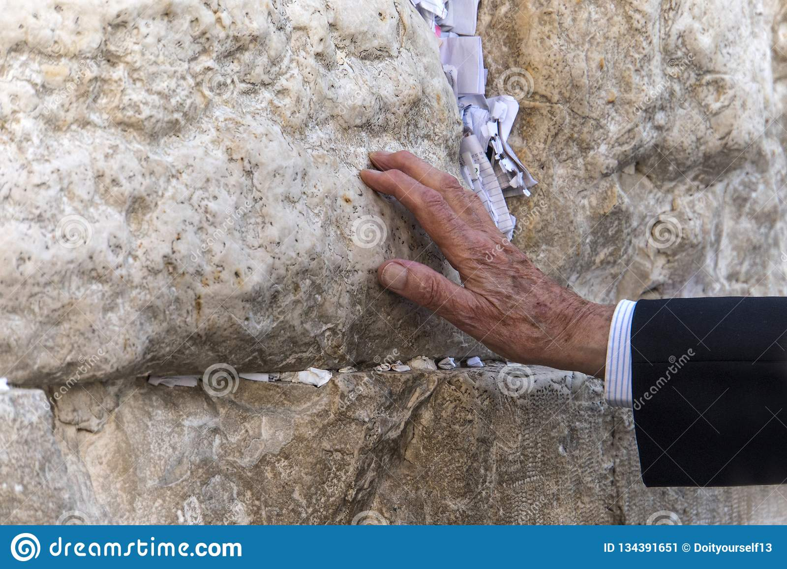 Hand van het bidden van de mens op de Westelijke Muur in Jeruzalem Raken de oude bejaarden een heilige steen in gebed Traditionel