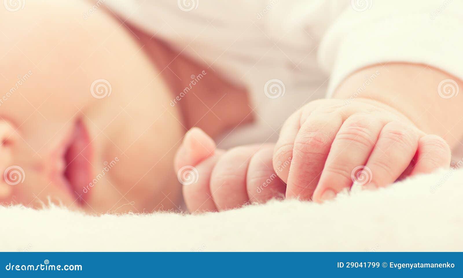 Hand van pasgeboren dichte omhooggaand van de slaapbaby
