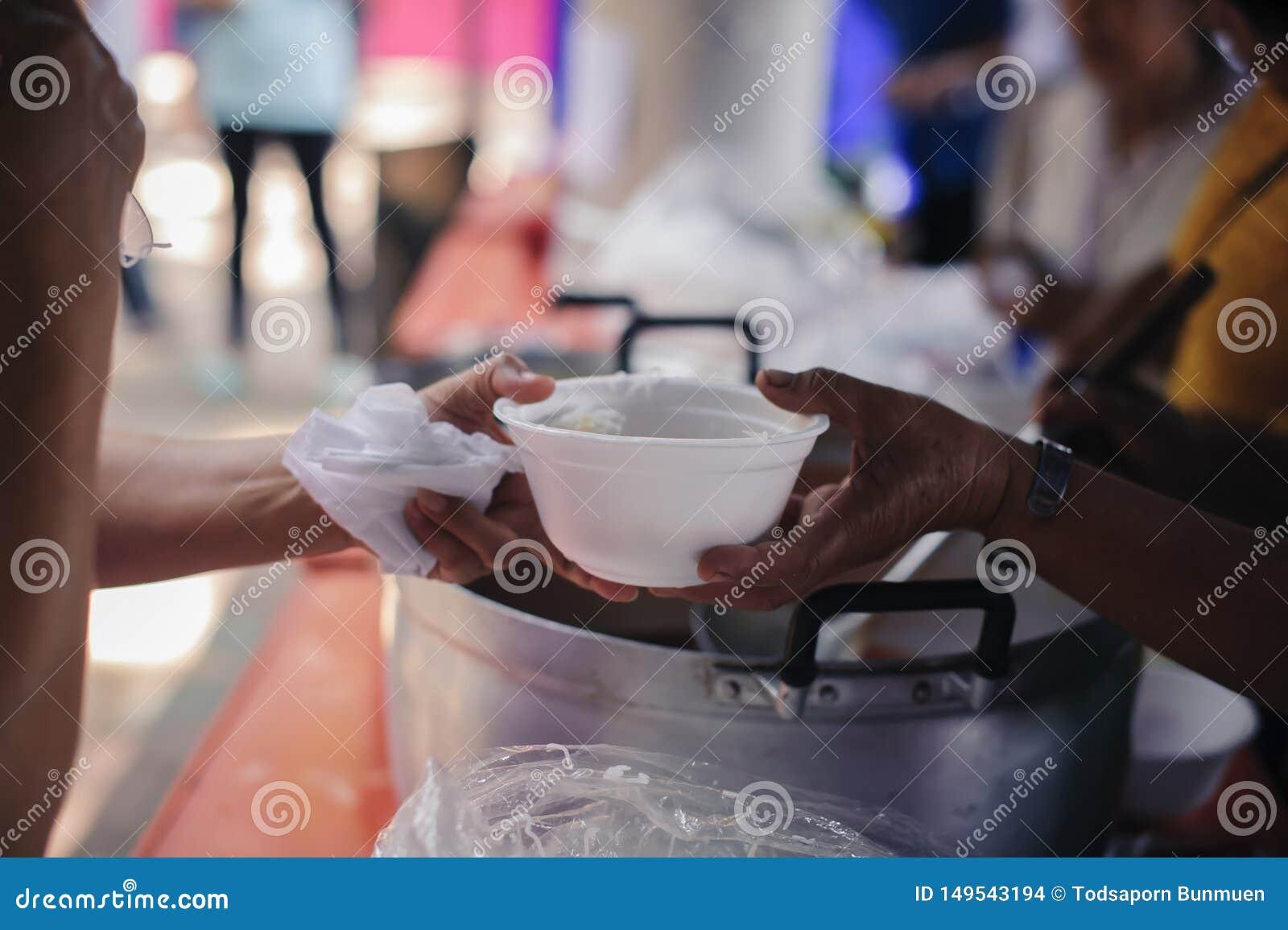 Hand-voedt aan behoeftig in de maatschappij: Concept het Voeden: De vrijwilligers geven voedsel aan de armen: het schenken van vo