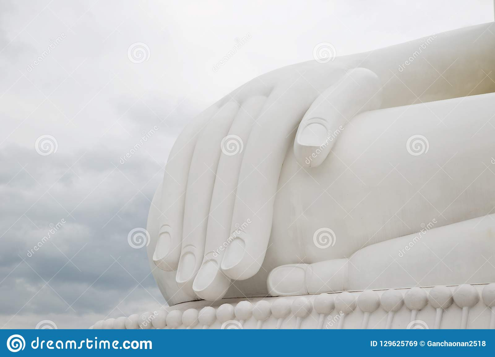 The hand of the white Buddha sky blue background.