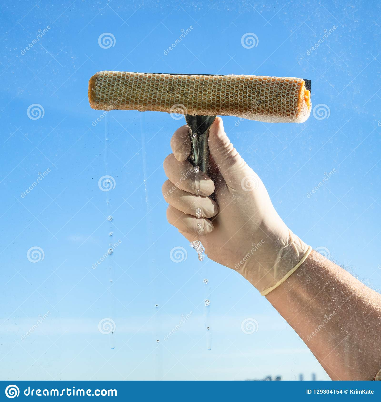 hand wipes a window with blue sky on background