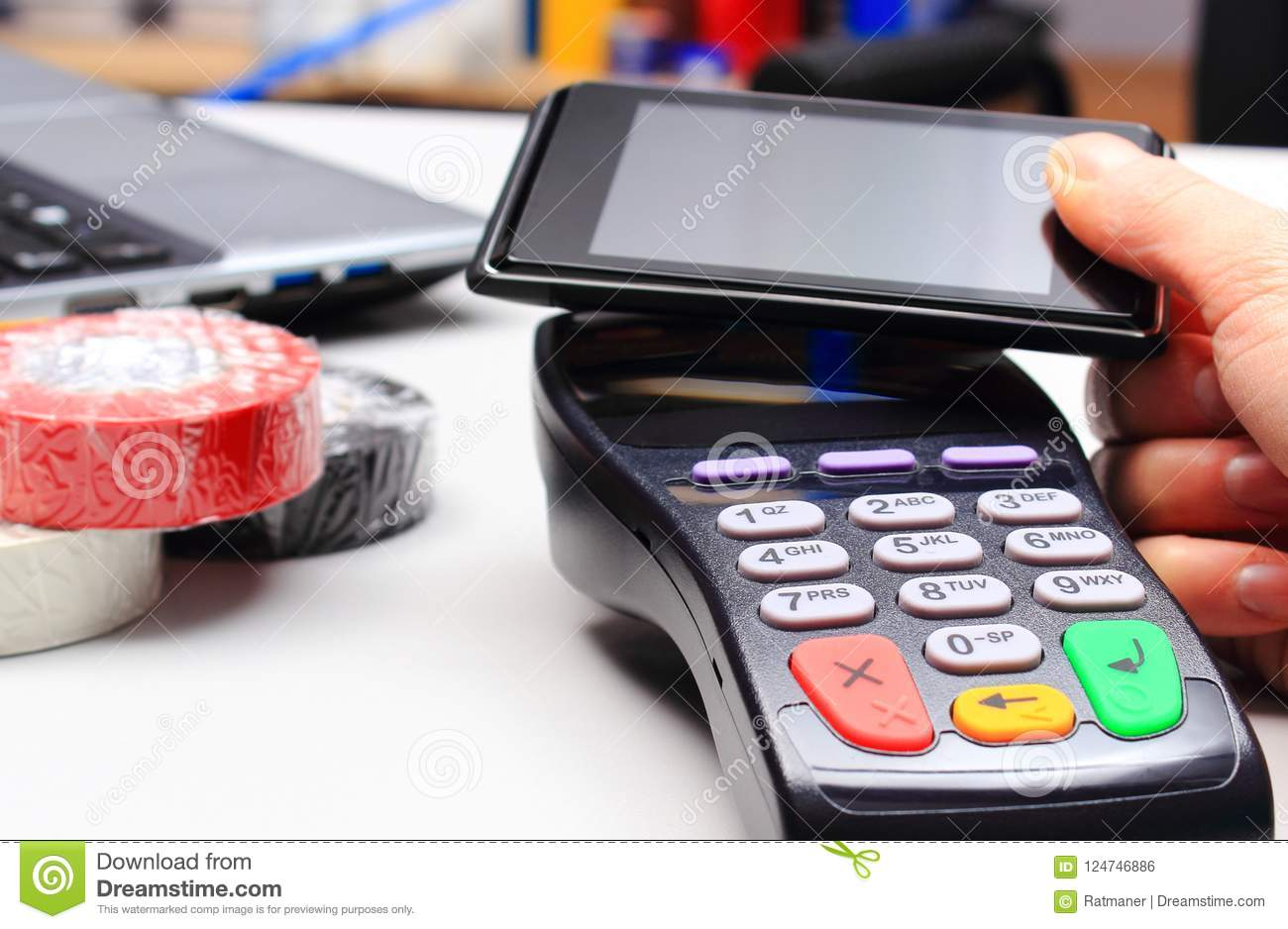 Hand of woman paying with credit card reader and mobile phone with NFC technology