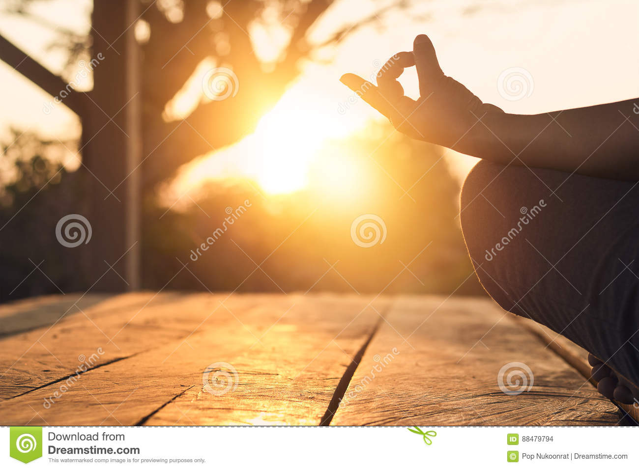 Hand of woman practicing meditation yoga on nature sunset