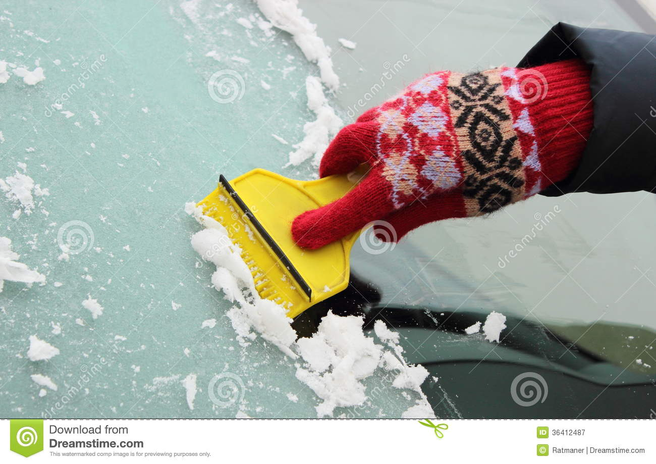 Hand Of Woman Scraping Ice From Car Windscreen Royalty