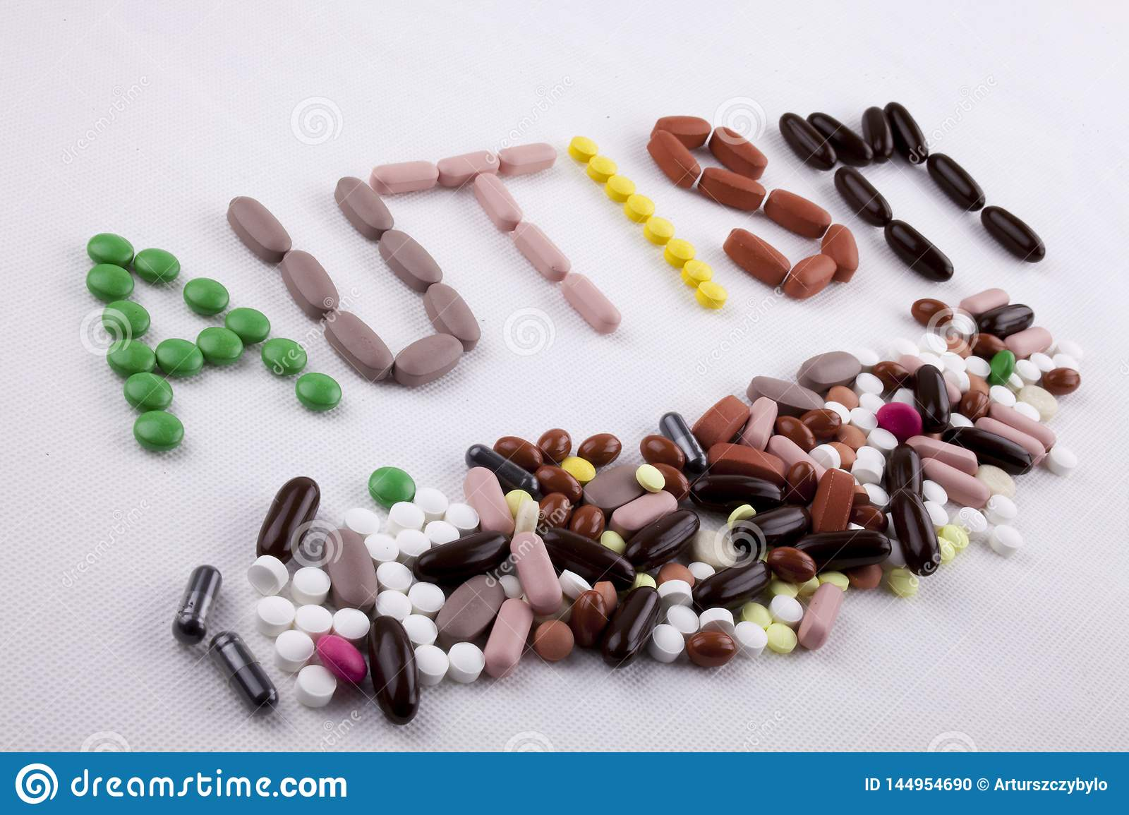 Hand writing text caption inspiration Medical care concept written with pills drugs capsule word AUTISM On white