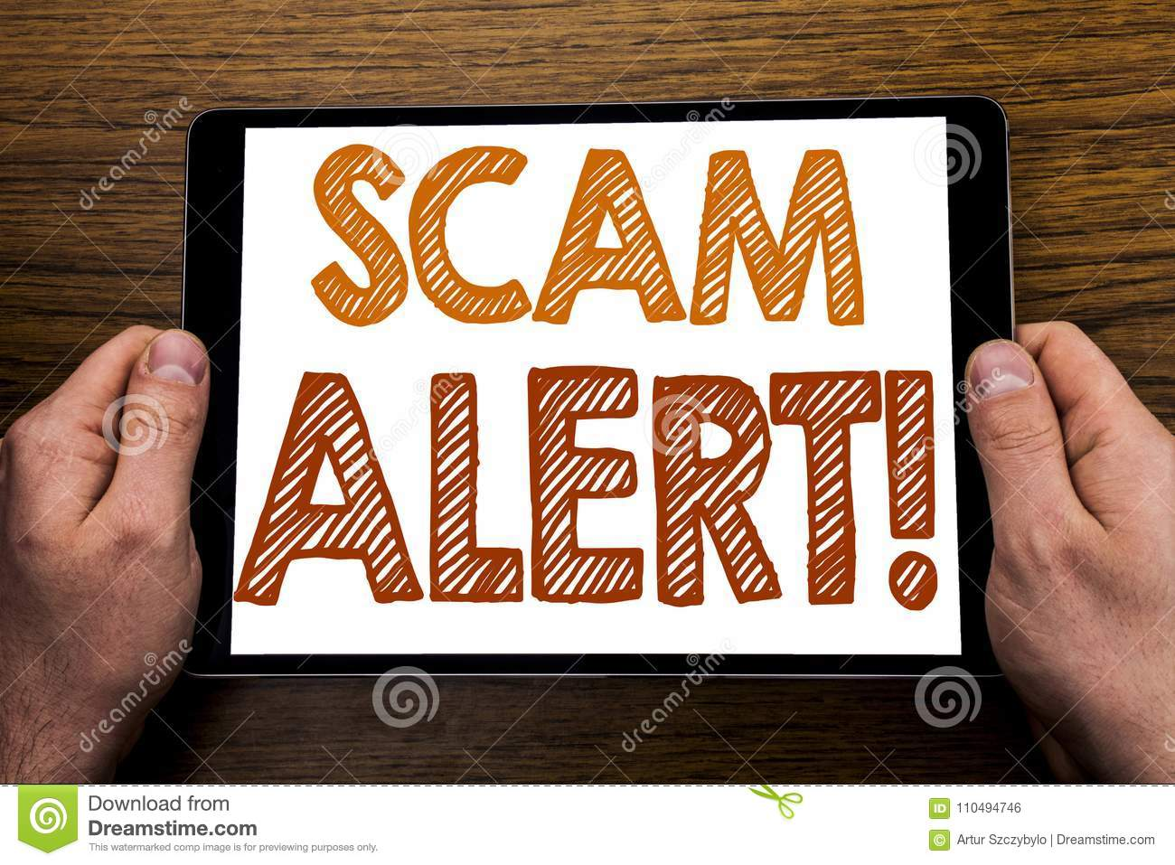 Hand writing text caption Scam Alert. Business concept for Fraud Warning Written on tablet laptop, wooden background with business