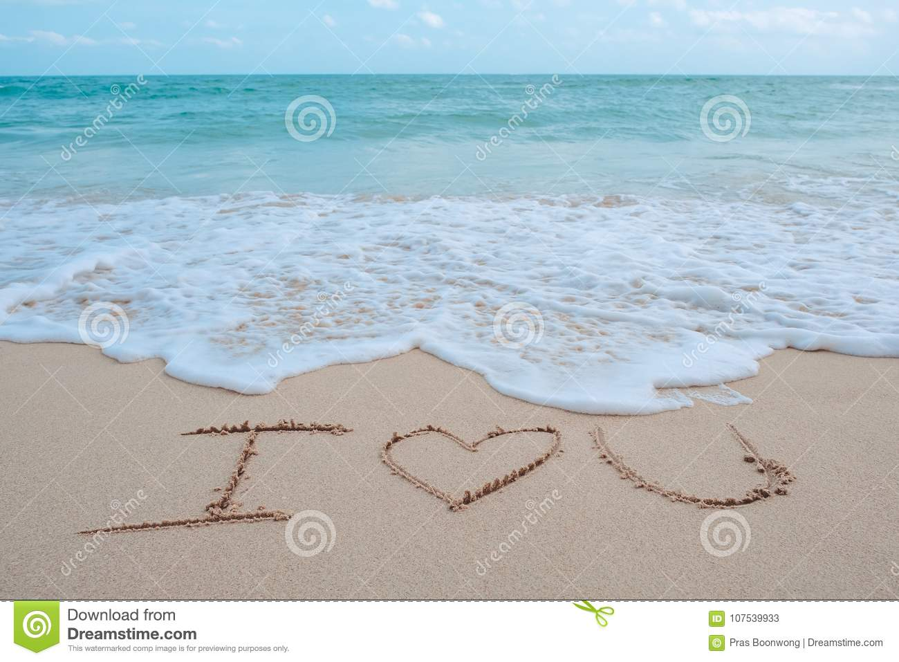 The hand writing word I love you on the beach by the sea with white waves and blue sky