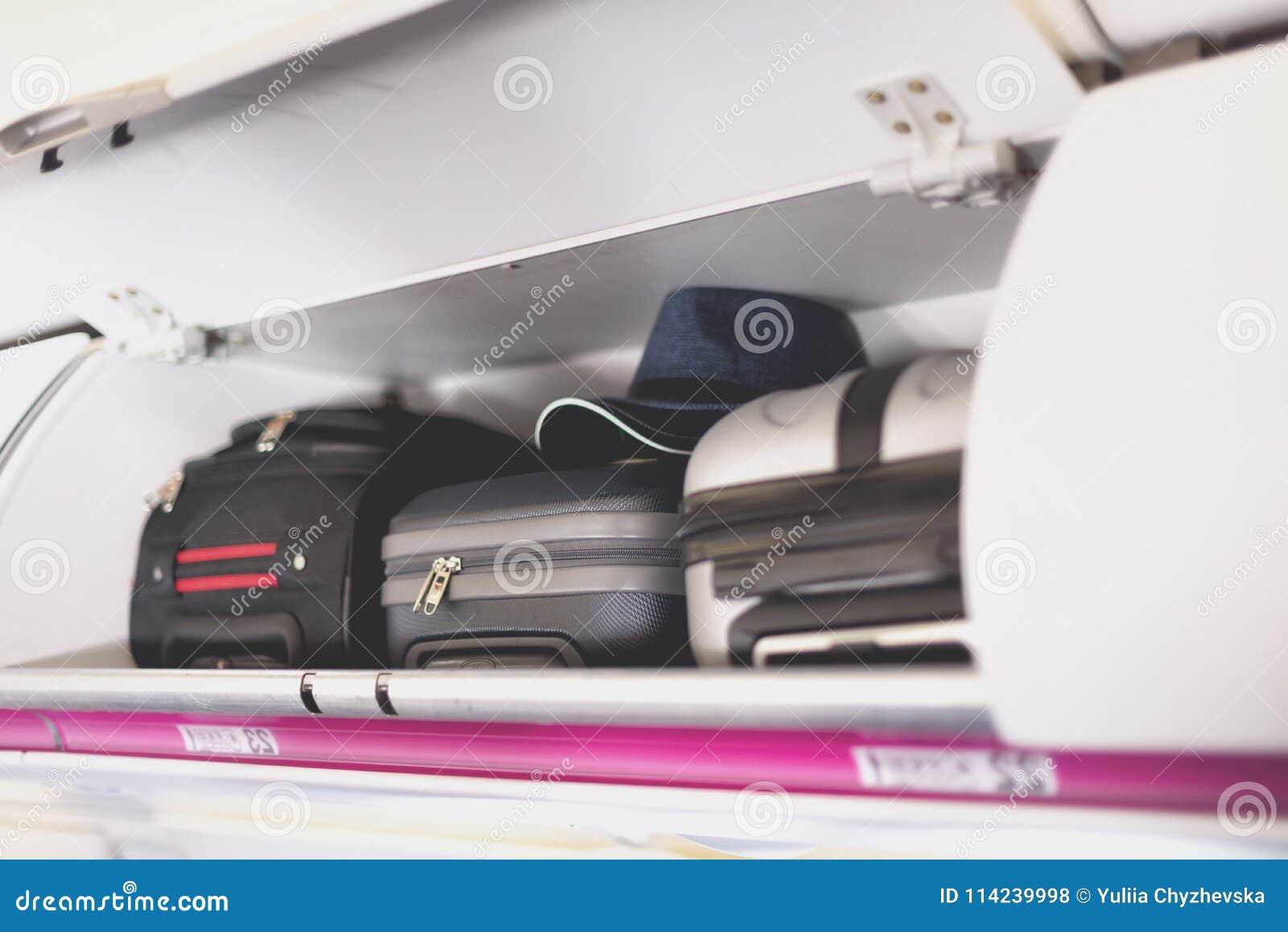 Handbagagerum med resväskor i flygplan Hylla för handbagagebagage överst av nivån Loppbegrepp med kopian
