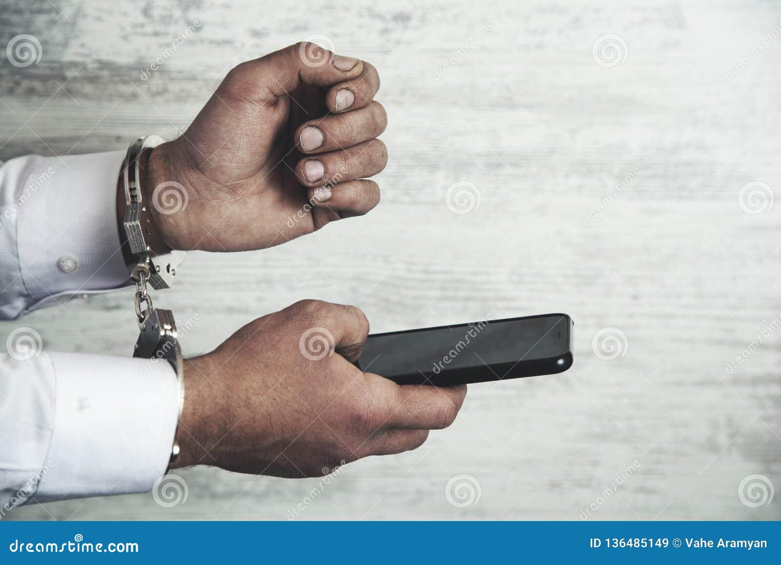 Handcuffs en de telefoon van de mensenhand