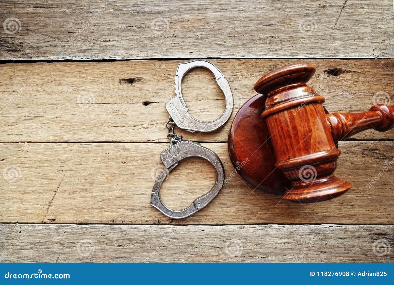 Handcuffs en rechtershamer bij het houten voorstellen die als achtergrond een misdaad proefoordeel beginnen