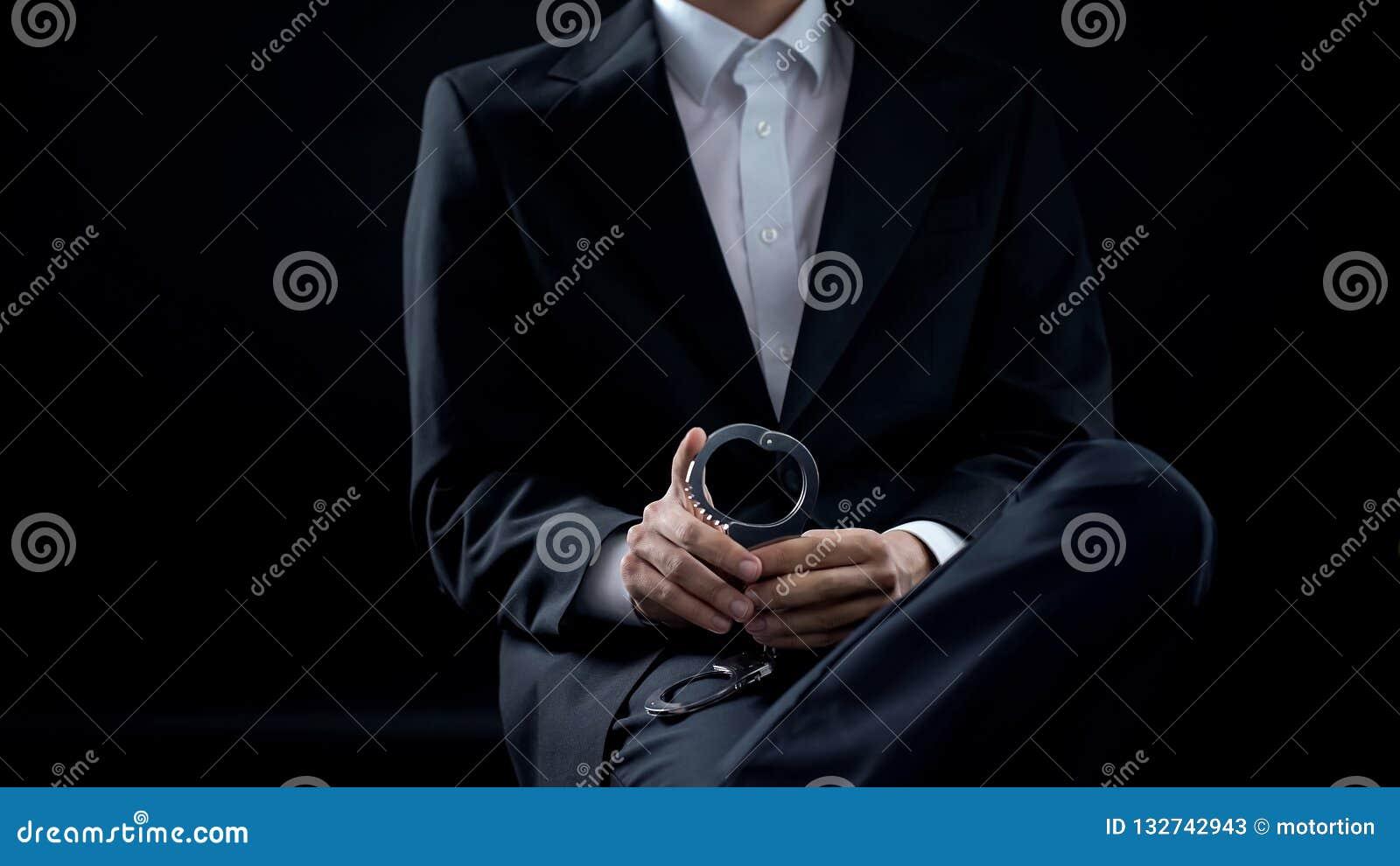 Handcuffs van de onderzoekersholding in handen, misdadige sanctie, wets en orderechtvaardigheid