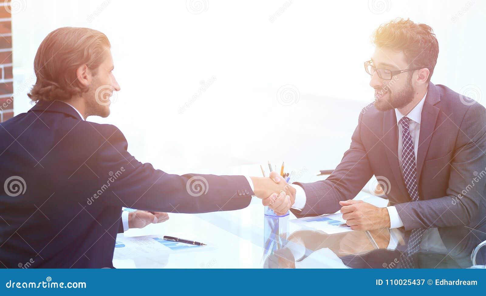 Handdruk van partners die bij hun Bureau zitten