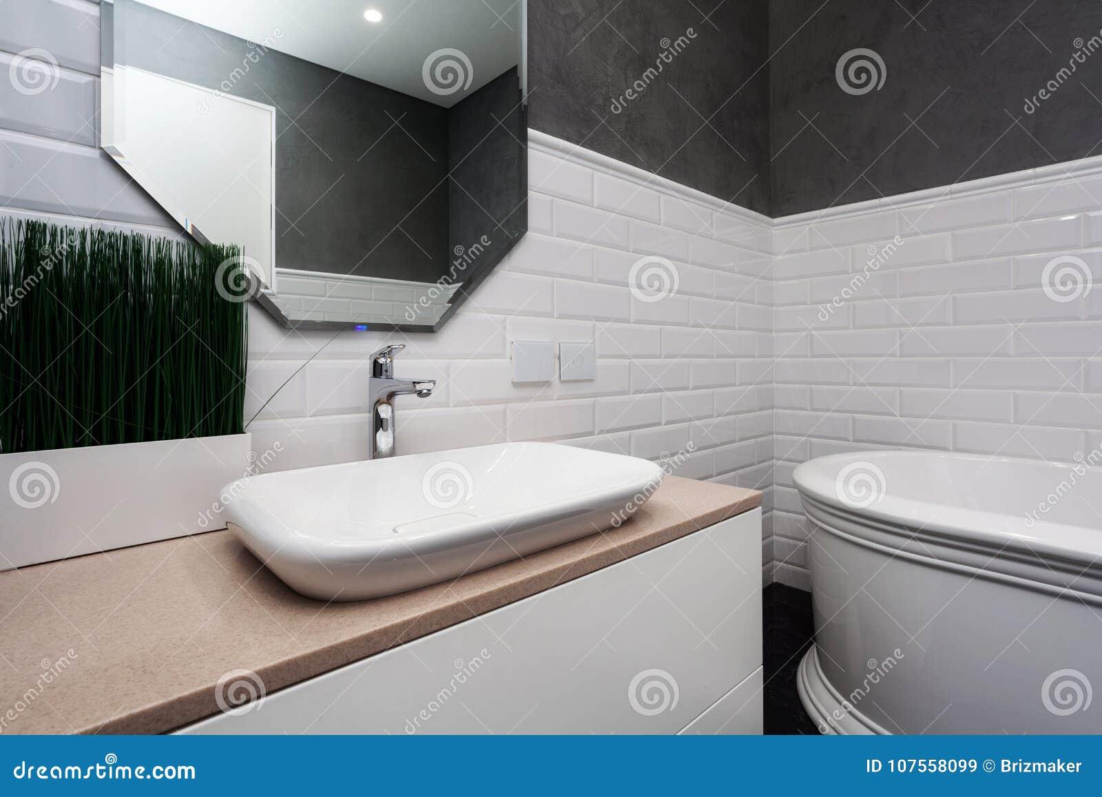 Handduk för badrumbunkeinterior Ljust badrum med nya tegelplattor Ny handfat, vit vask och stor spegel