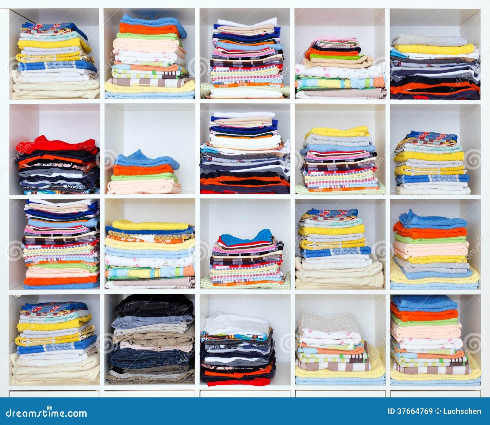 Handdukar, sängark och kläder på hylla