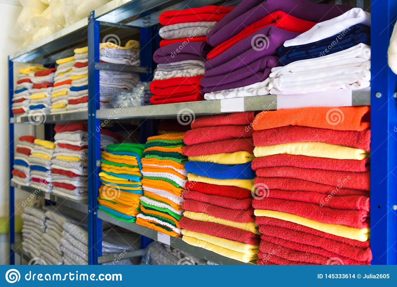 Handdukar, sängark och kläder på hyllan