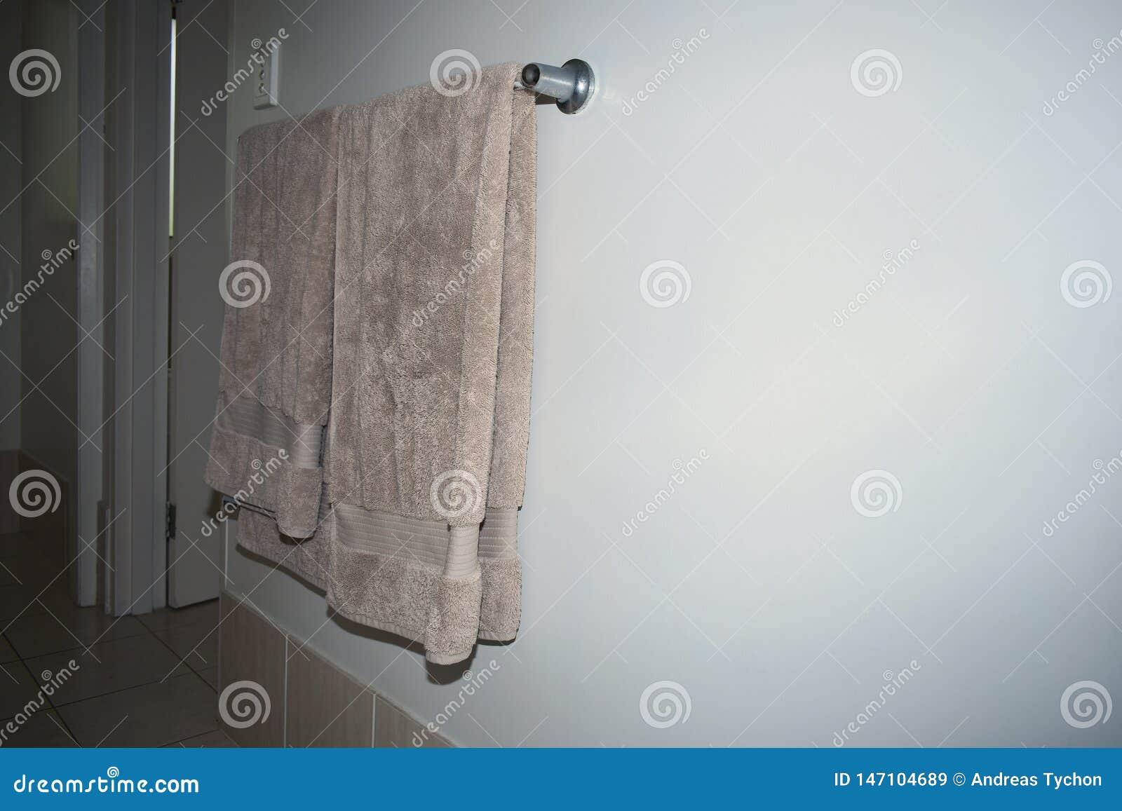 Handdukar som draperas över en stång för handduk för kromstål på en vägg