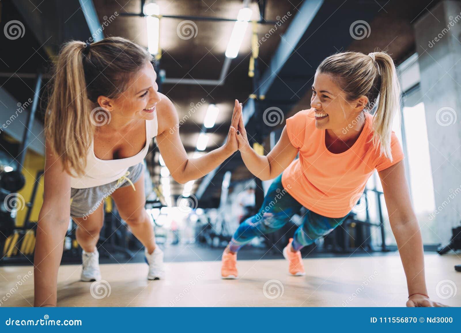 Handeln mit zwei drückt das sportliche Mädchen ups in Turnhalle