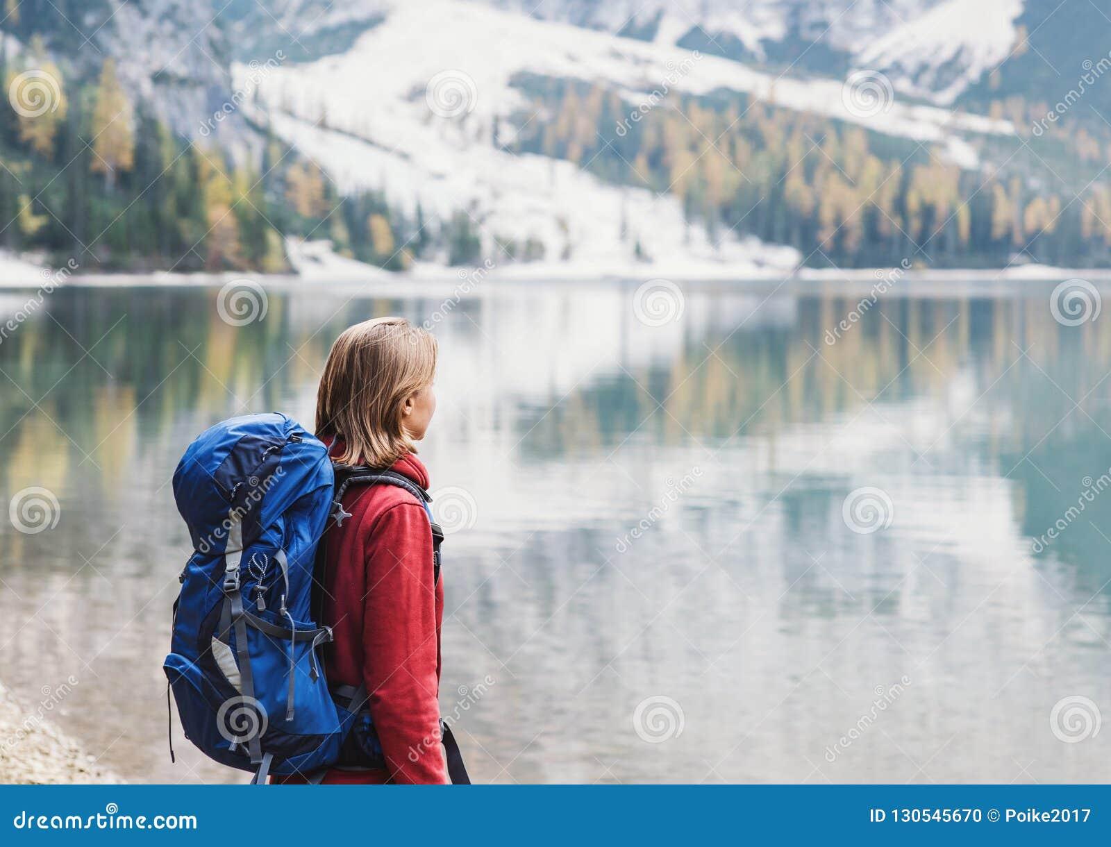 Handelsresande för ung kvinna i fjällängberg som ser på en sjö Lopp, vinter och aktivt livsstilbegrepp