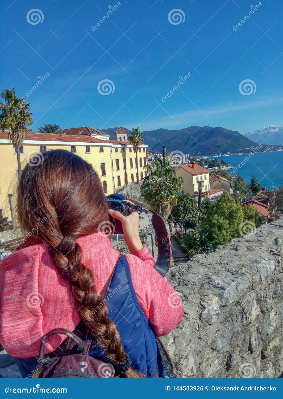 Handelsresande för ung kvinna som fotograferar med staden och berg för yrkesmässig fotokamera den gamla