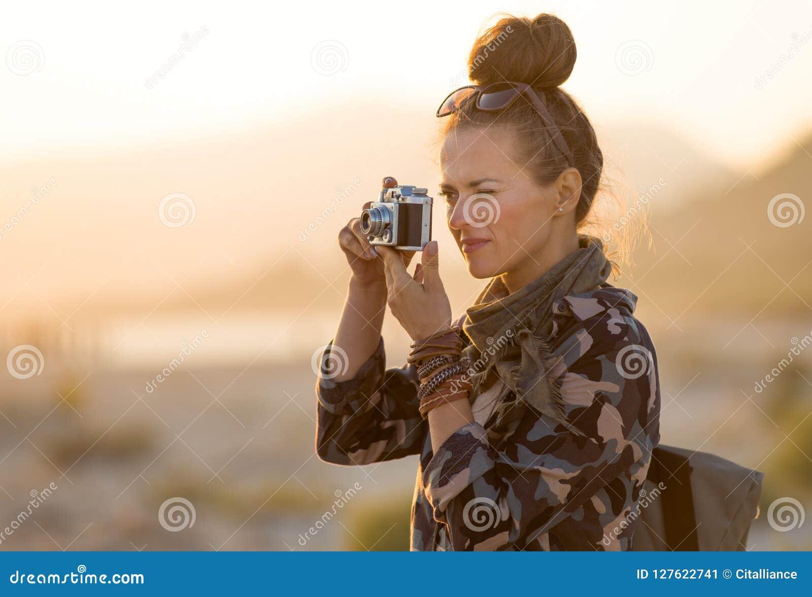 Handelsresandekvinna som tar foto med den retro fotokameran