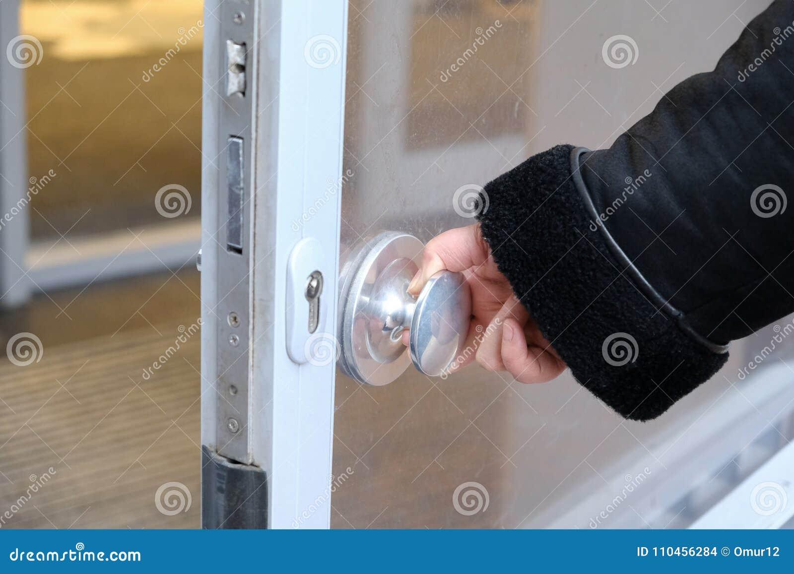 Handen öppnar dörren vid handtaget