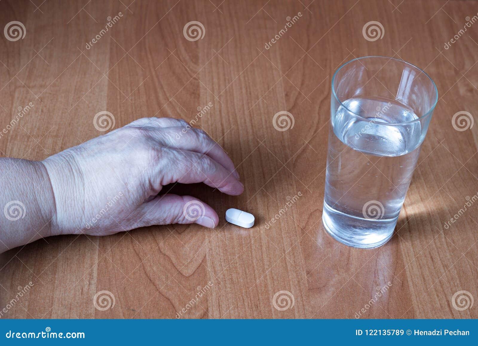 Handen av en äldre kvinna tar en preventivpiller, ett exponeringsglas av vatten, en närbildpreventivpiller