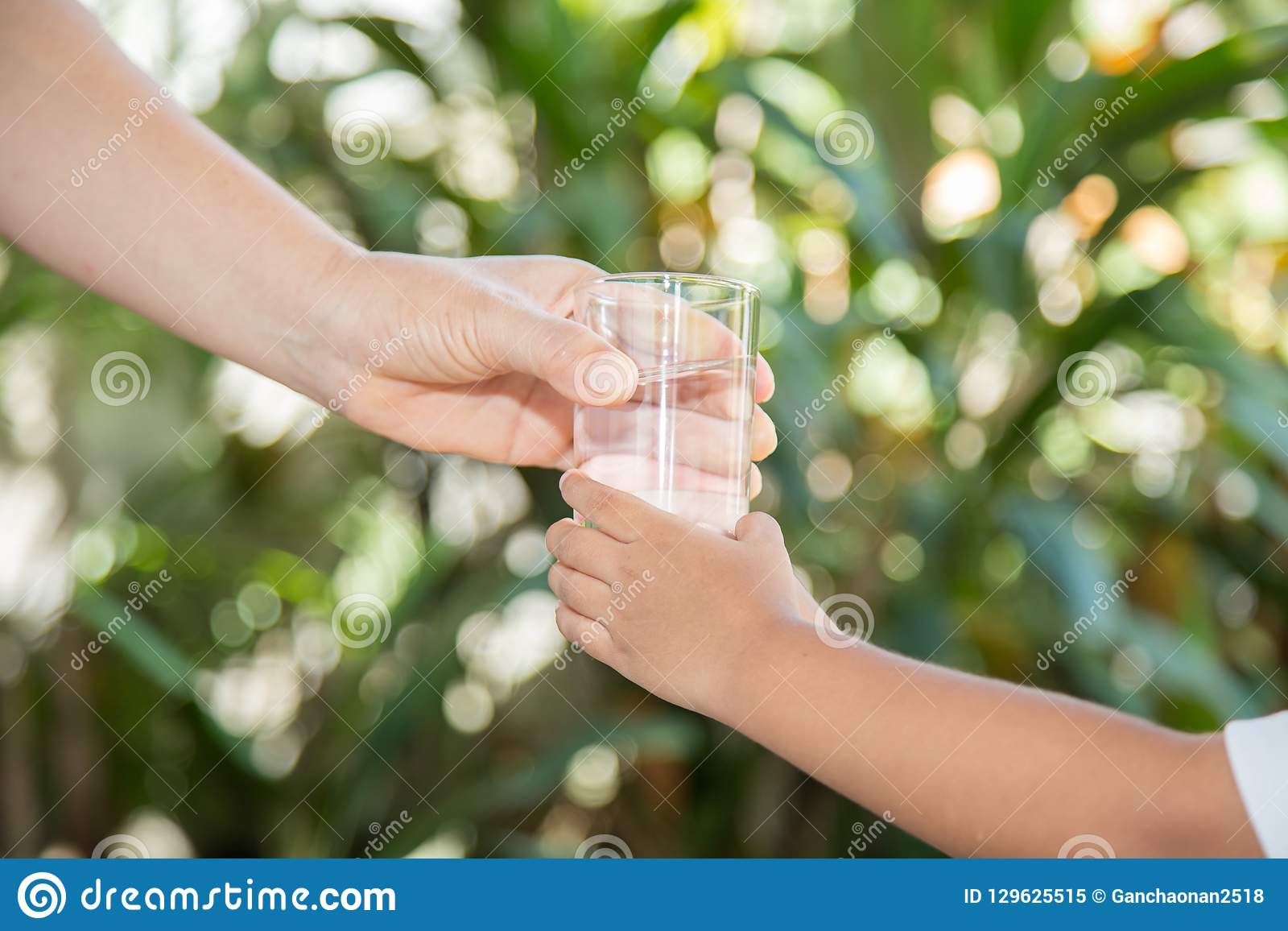 Handen av en kvinna rymmer ett exponeringsglas till pojkens hand