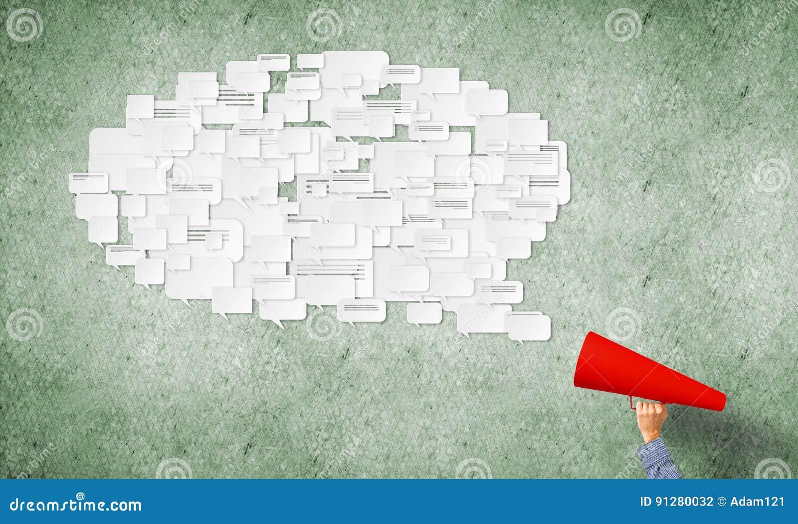 Handen av mannen som rymmer den röda pappers- trumpeten, och anförande fördunklar