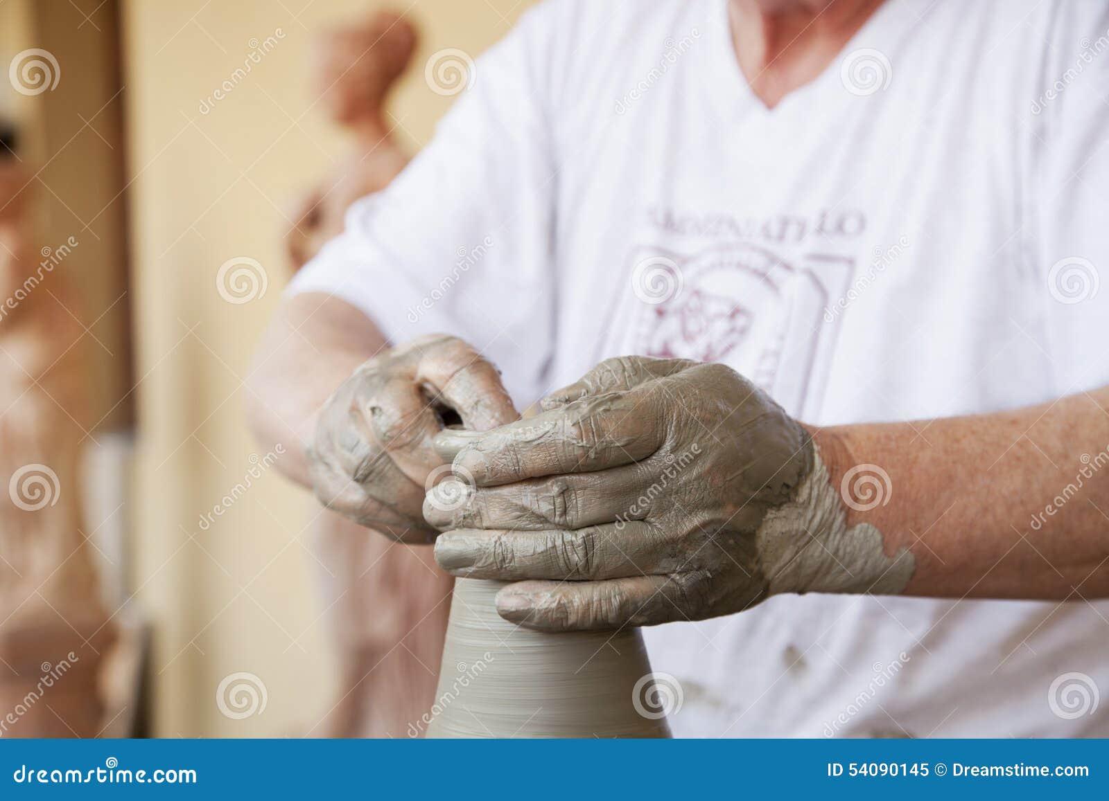 Handen die de klei werken