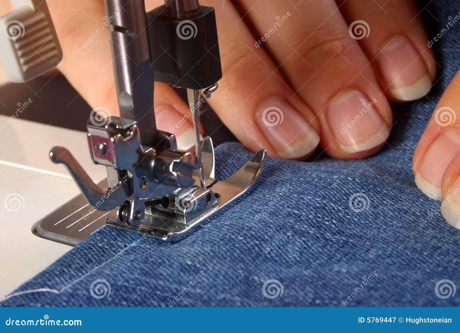 Handen die een naaimachine met behulp van