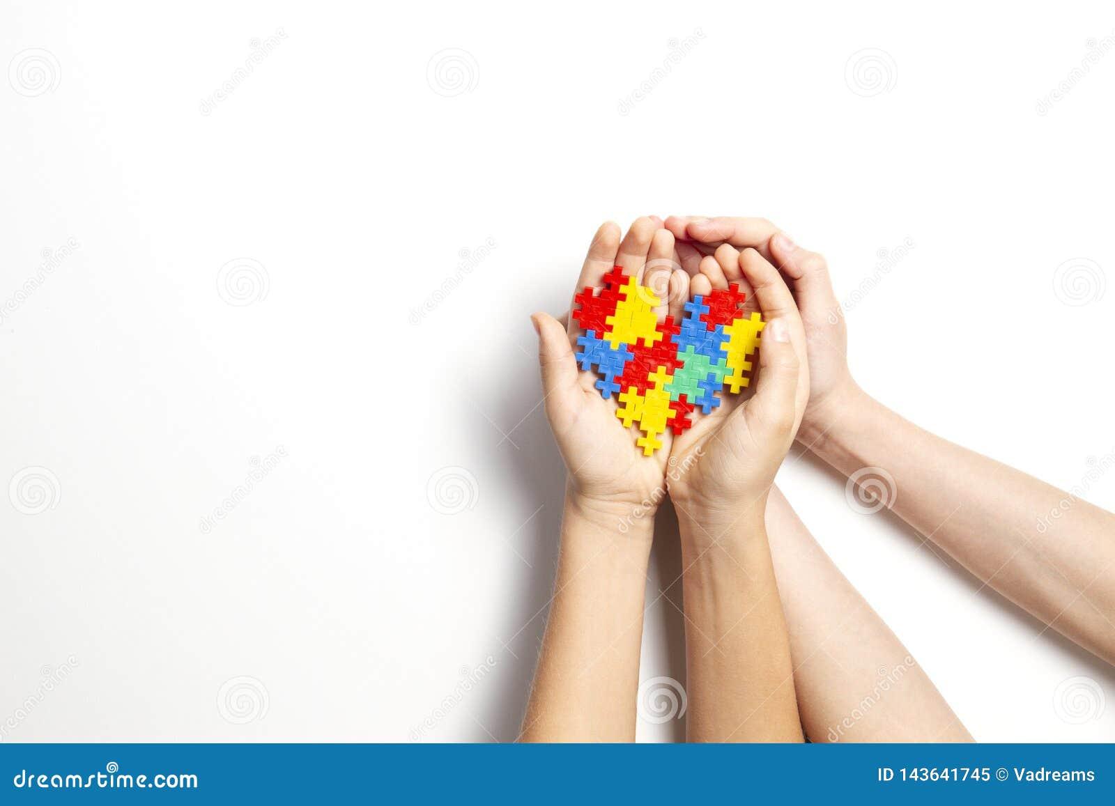Handen die kleurrijk hart op witte achtergrond houden Het concept van de de voorlichtingsdag van het wereldautisme