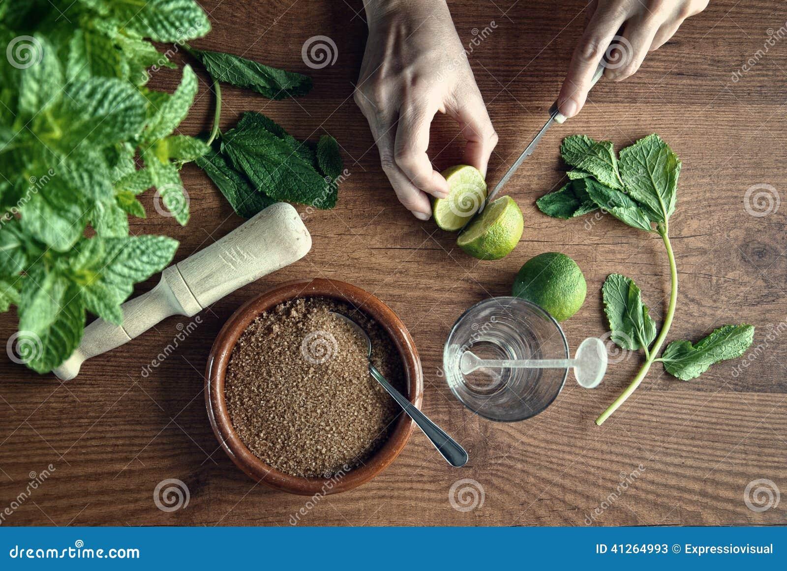 Handen die mojitococktail voorbereiden