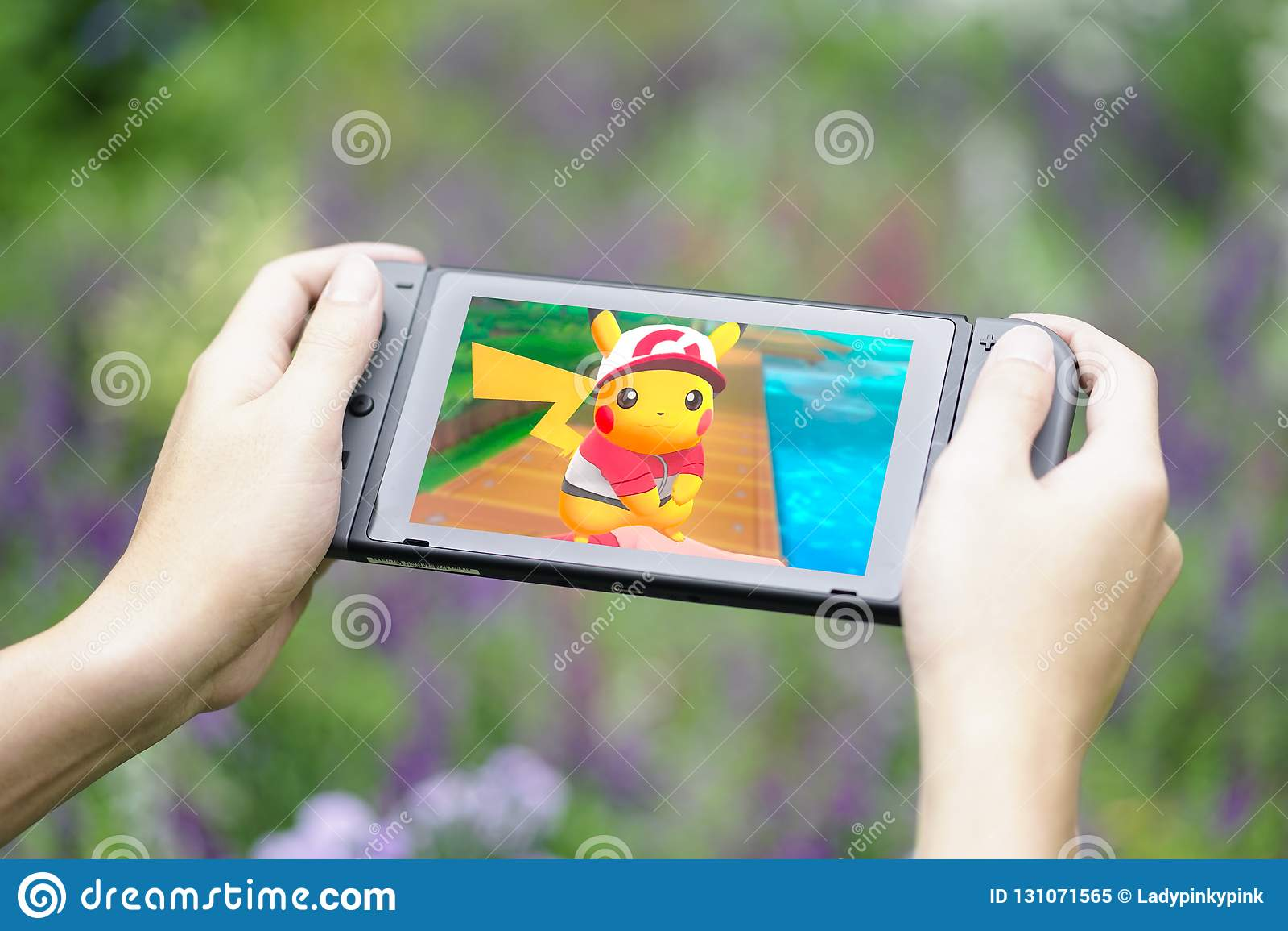 Handen die van gamer Nintendo-Schakelaar houden terwijl het spelen Pokemon Pikachu in de tuin gaan
