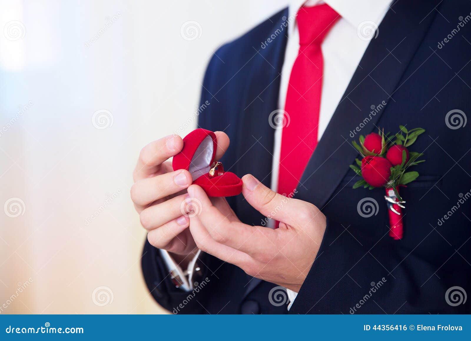Handen die van huwelijksbruidegom klaar in kostuum worden De bruidegom houdt Th