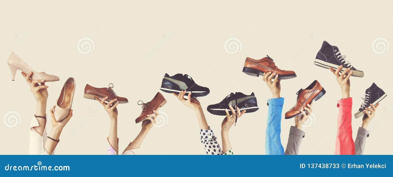 Handen die verschillende schoenen op geïsoleerde achtergrond houden