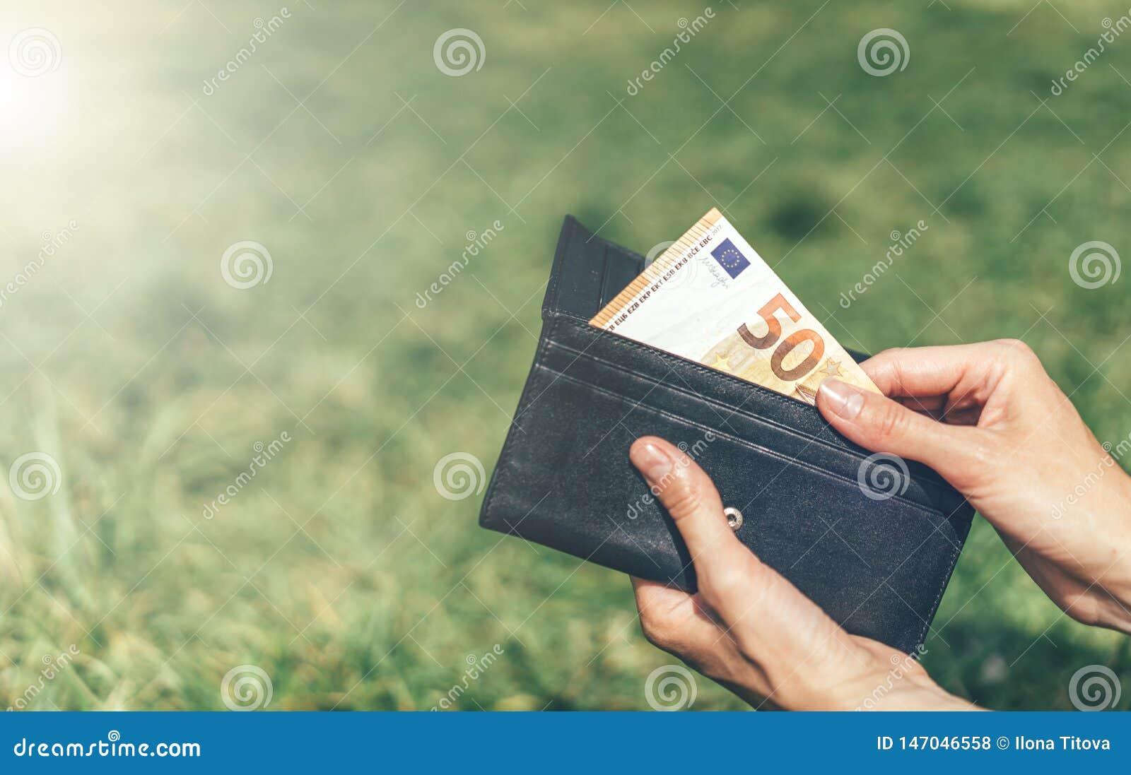 Handen drar en räkning av 50 euro från plånboken