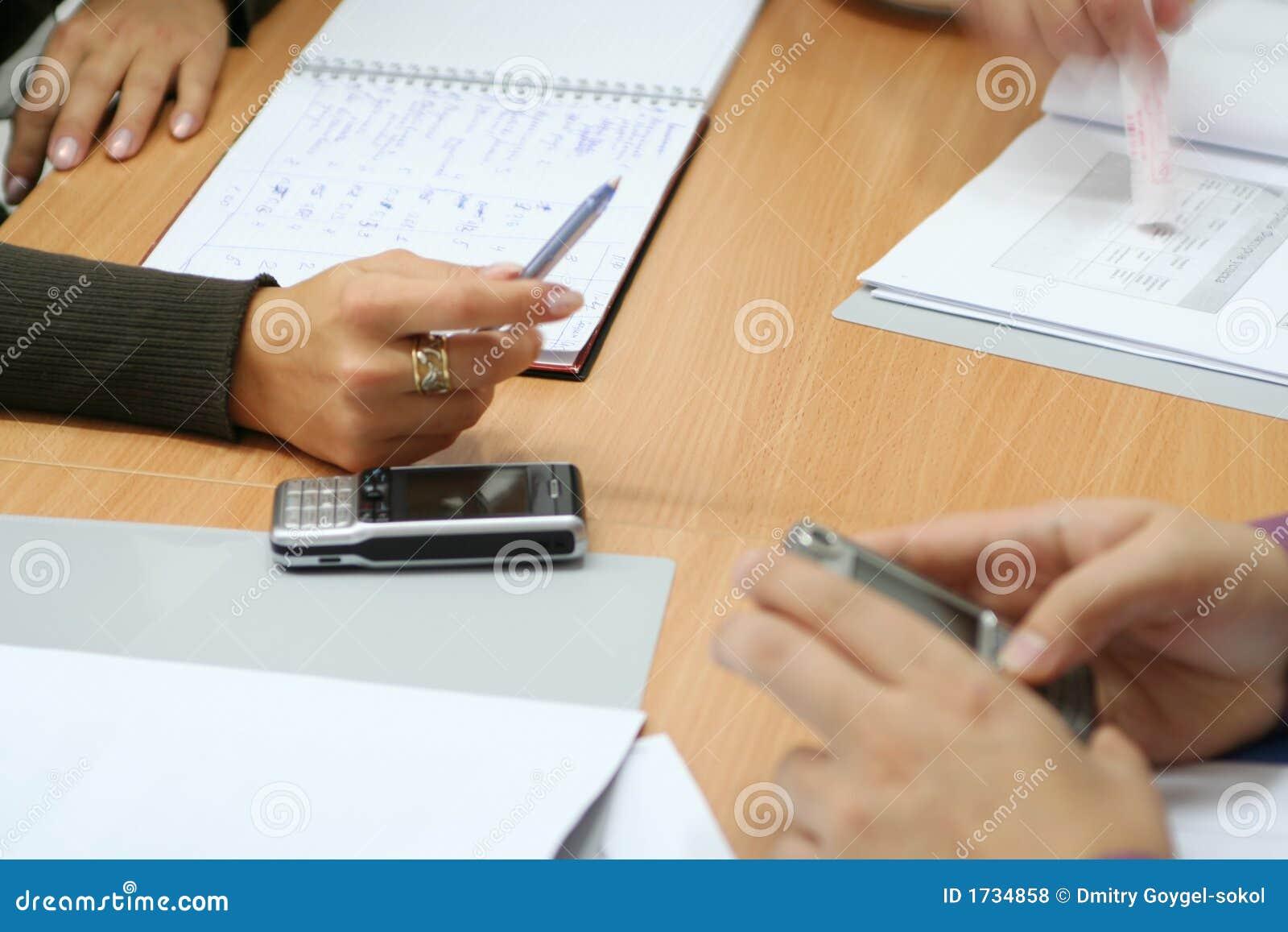 Handen en mobiles in het bureau