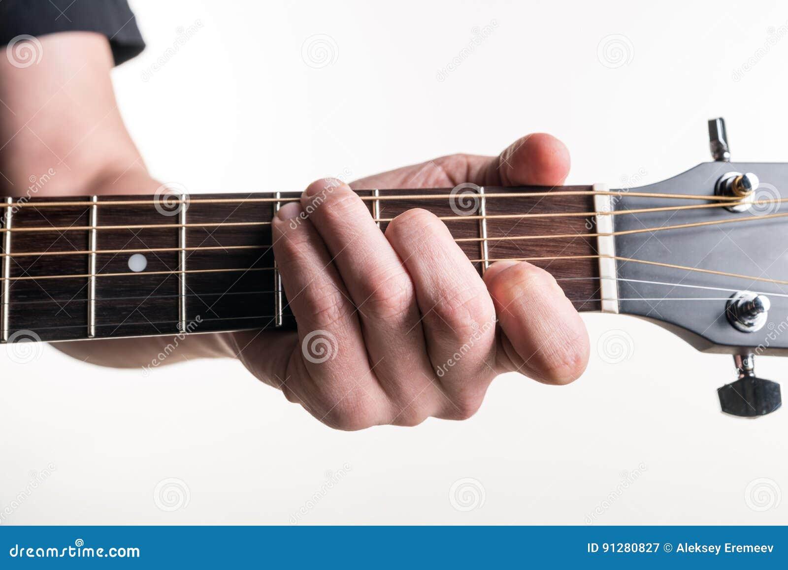 Handen för gitarrist` s klämmer fast ackordet C på gitarren, på en vit bakgrund Horisontal inrama