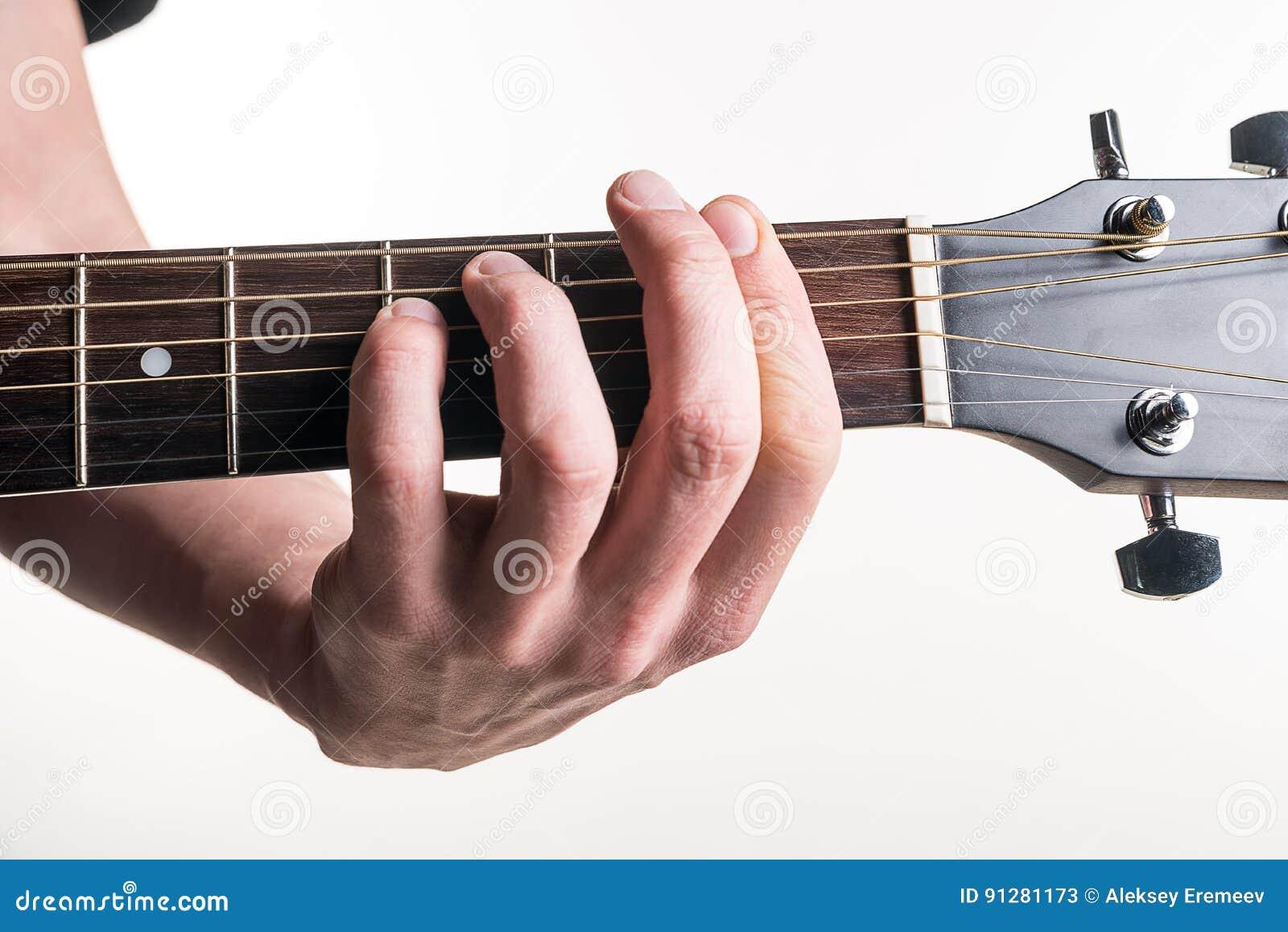Handen för gitarrist` s klämmer fast ackordet Fm på gitarren, på en vit bakgrund Horisontal inrama