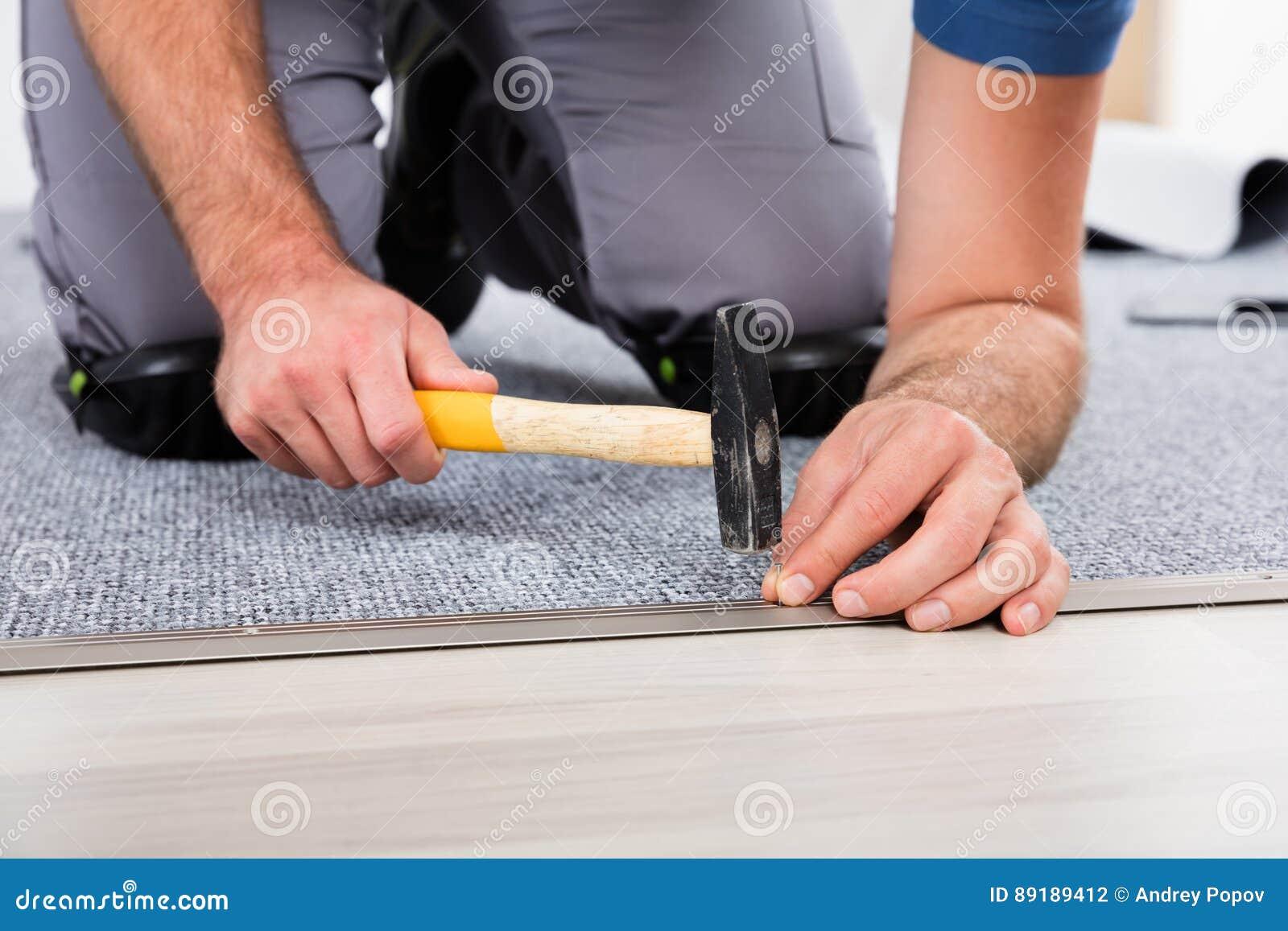 Handen för person` s genom att använda hammaren och spikar
