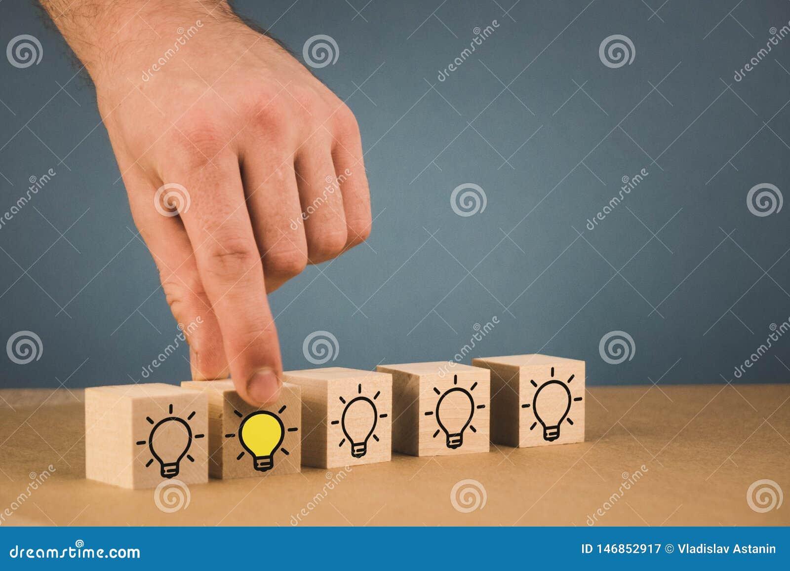 Handen g?r ett val och v?ljer en brinnande ljus kula, ett symbol av en ny id?