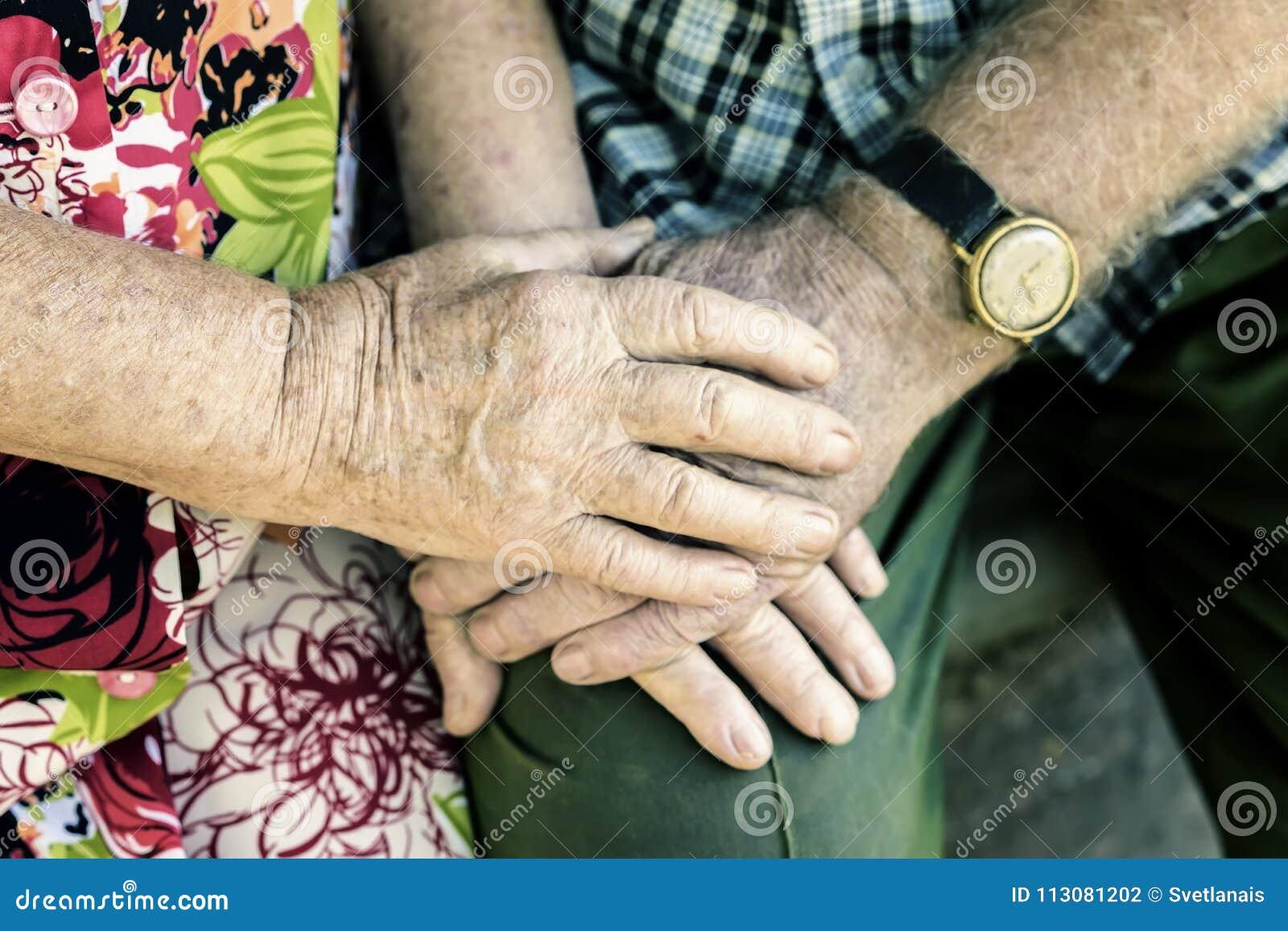 Handen met rimpels die van bejaard paar, handen van oudsten samen close-up houden, concept verhoudingen, huwelijk