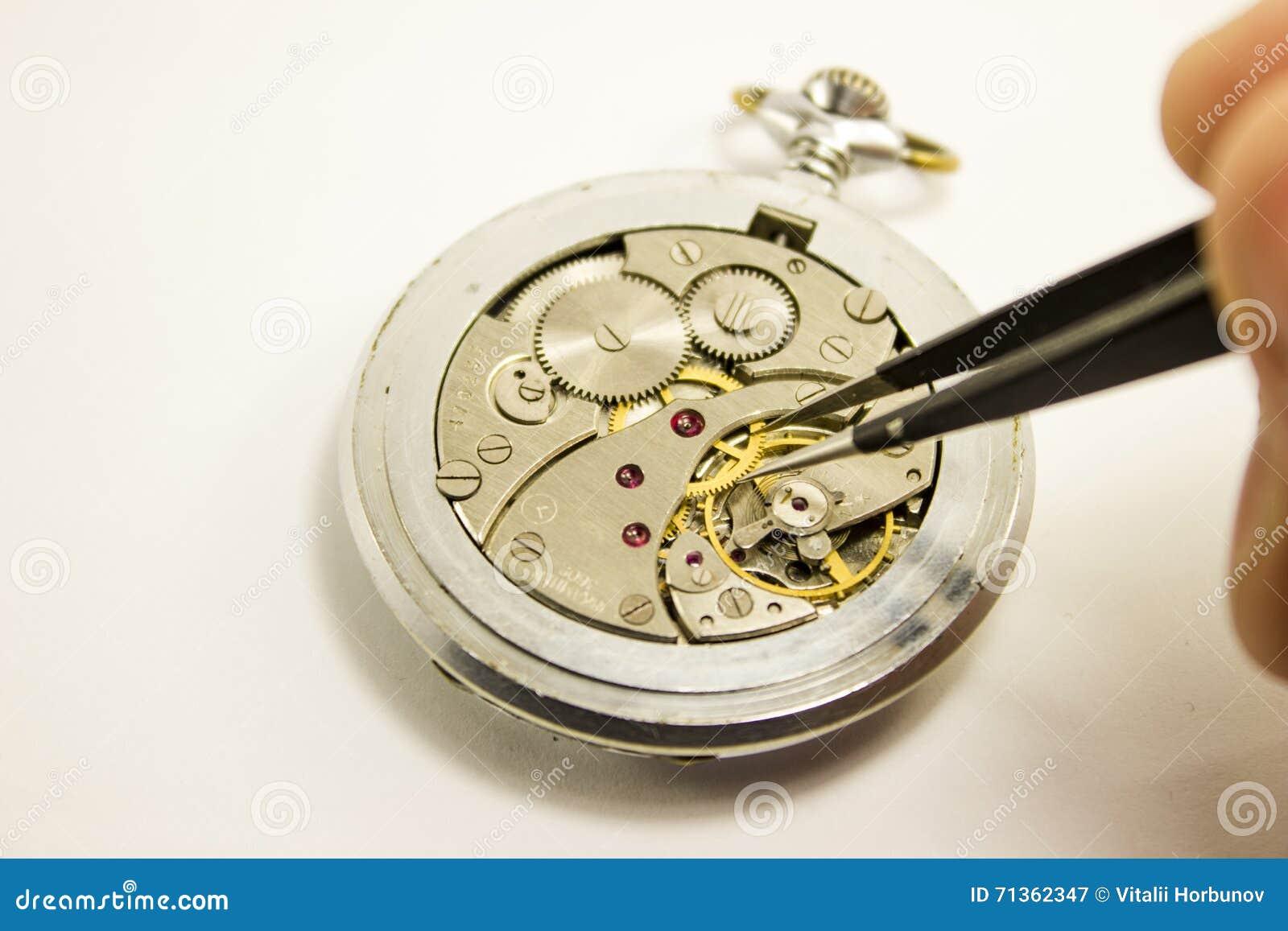 Handen reparerar den mekaniska klockan på vit bakgrund
